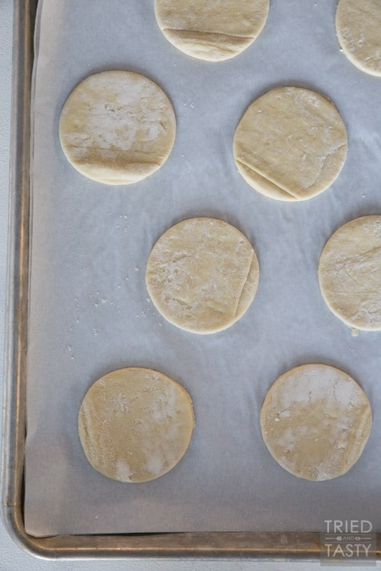 Silver cookie sheet with parchment paper topped with six 2-inch circle puff pastry