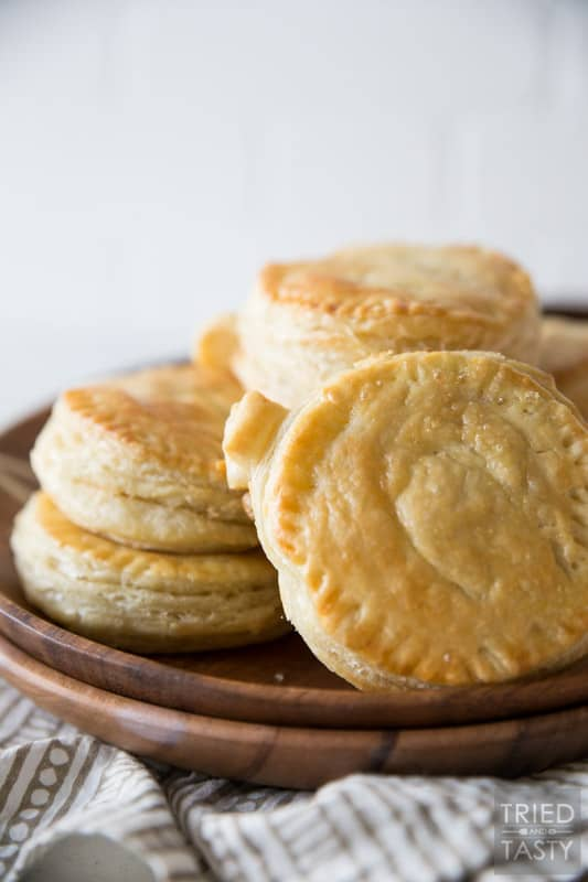 A finished plate of golden brown pumpkin shaped hand pies stacked on top of each other on a wooden brown plate