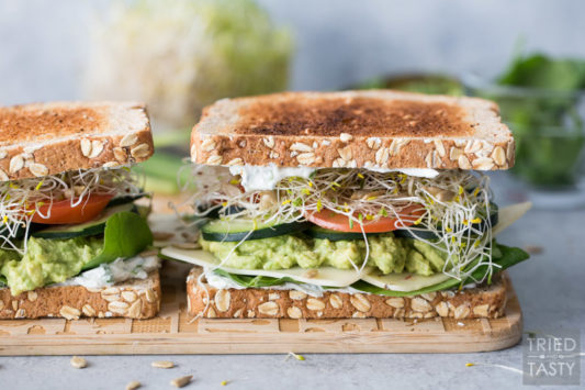 A close up photo of a Veggie Sandwich on a wooden cutting board