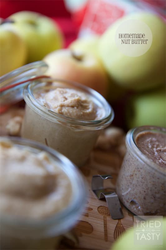 Close up shot of small clear jars with homemade nut butter with apples and nuts in the background.