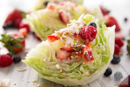 Mixed Berry Wedge Salad // Seve this at your next BBQ! You only need a handful of ingredients including: fresh lettuce, in-season berries, dressing and cheese. The crowd will go nuts with the stunning side dish!   Tried and Tasty