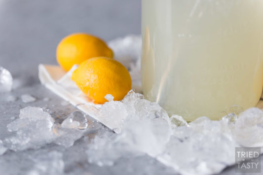 Ice on a table with two lemons & a jar of lemonade
